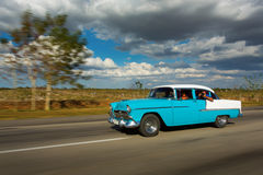 Old classic car on street of Cuba with white clouds and blue sky Stock Photos