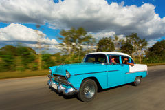 Old classic car on street of Cuba with white clouds and blue sky Royalty Free Stock Photo