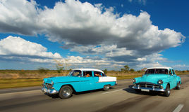 Old classic car on street of Cuba with white clouds and blue sky Stock Photo