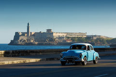 Old classic car on street of Havana with ocean and lighthouse in Royalty Free Stock Photography