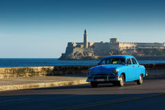 Old classic car on street of Havana with ocean and lighthouse in Stock Image