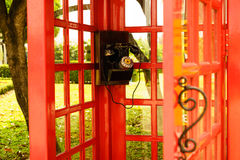 Old classic dial phone. In red booth Royalty Free Stock Image