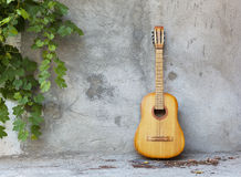 Old classic guitar standing against grungy wall Royalty Free Stock Image