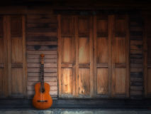 Old classic guitar on wood wall. Old classic guitar on Texture of old Wood Door and Wall Front Home Stock Photos
