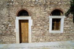 Old classic little church arch door and window frame on earth tone natural stone wall facade background with marble curb in front. Athens, Greece Stock Images