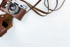Old classic photo camera in brown leather case on white wooden d. Old classic photo camera in brown leather case on white wooden surface flat view Royalty Free Stock Photo