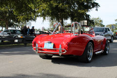 Old classic red sports car driven on road Royalty Free Stock Photography