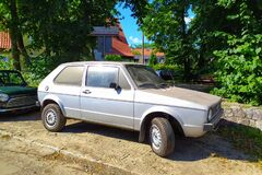 Old vintage dusty light grey VW Golf one parked