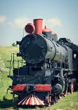 Old classic train to the red tube on a background of green grass. Stock Photo