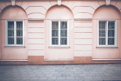 Old classical building wall with windows and pavement as as architectural background Stock Photos