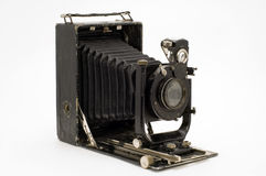 Old classical camera with furs. The old photographic chamber with a lens of furs on a white background Stock Photography