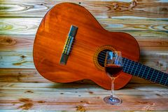 Old classical guitar on wooden background and a glass of wine stock image