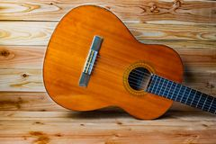 Old classical guitar on wooden background stock photos