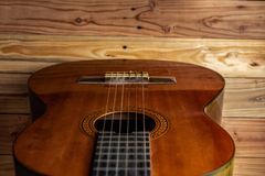 Old classical guitar on wooden background stock images