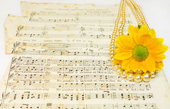 Old classical music scores with pearls and flower Royalty Free Stock Image
