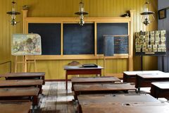 Old classroom with blackboard and school benches. Old desk, lamps, abacus and other school objects Royalty Free Stock Photos