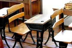 Old classroom with vintage desks. This is an old schoolhouse classroom with vintage desks.  These were the types of retro desks that children sat in while royalty free stock image