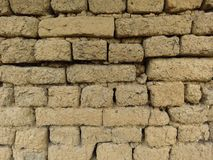 Old clay brickwork wall. Wall clay bricks and cracks suitable for rustic retro style background. Space for text. Claybrick texture yellow grey colours royalty free stock photography