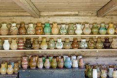 Clay containers on a shelf. Old clay dishes stand on shelf Royalty Free Stock Photos