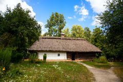 An old clay house, a roof of reeds royalty free stock photography