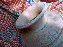 Old clay jar on red and green Batik fabric background Royalty Free Stock Photos