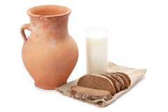 Old clay jug, a glass of milk and bread Stock Image