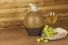 Old clay jug and a glass of wine on a wooden table. White wine and snacks. Ham, cheese and grapes to eat. Royalty Free Stock Photo