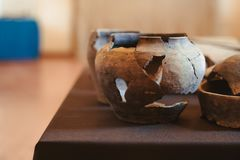 Old clay jug with cracks. An old clay jug with large cracks stands on the shelf stock photo
