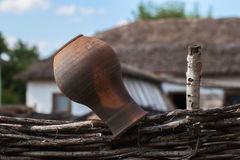 Old clay Jug on a wicker fence, rustic style, rural scenery Stock Image