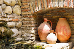 Old clay jugs in the brick and stone place. Background Royalty Free Stock Images