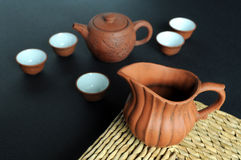 Old clay pot and tea-set. An old Chinese tea-set with a pot rest on grass mat Royalty Free Stock Photography