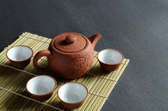 Old clay pot and tea-set. A set of Chinese tea drinking utensil rests on bamboo mat Royalty Free Stock Photography