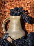 Old clay wine jug surrounded by black grape bunches and winemaking emblem. With cork with wicker basket as a background Royalty Free Stock Image