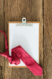 Old clipboard, red necktie on grungy wooden surface Royalty Free Stock Photography