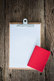 Old clipboard, red notebook on grungy wooden surface royalty free stock photos