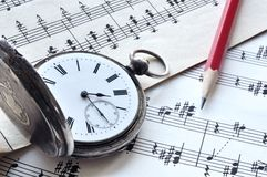 Old clock. And red pencil on music book Royalty Free Stock Images