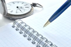 Old clock. Notebook and blue pen Royalty Free Stock Photo