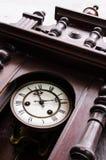 Old clock. Closeup of antique beautiful wooden pendulum clock Stock Photo