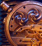 Old Clock. Old invention. The mechanism of a watch with a yellow glow. Blue glare. Details are visible. Inscriptions indicate how to adjust and are not logos Stock Image