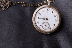Old clock on a background of black leather Royalty Free Stock Photo