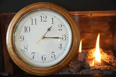 Clock on the background of a burning fire in the fireplace royalty free stock image