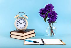Old clock on books, blue flower color and notebooks on blue background blog concept image. Old retro clock on books, purple flower in vase and notebooks on blue royalty free stock photo
