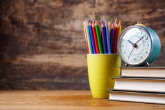 An old clock on the books on the table at the student stock photo