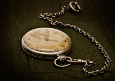 Old clock with chain lying on rough green surface Stock Photography