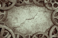 Old Clock Cogs Frame. Grunge background frame from old cogs surrounding cracked wall with split tone effect Royalty Free Stock Images