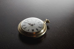 Old watches on the desk. Old silver pocket watch placed on the dark wooden table Royalty Free Stock Photos