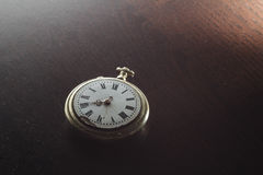 Old clock on the desk. Old silver pocket watch placed on the dark wooden table Stock Photography