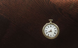 Old clock on the desk. Old silver pocket watch placed on the dark wooden table Royalty Free Stock Image