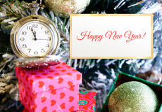 Old clock almost 12 on dial with festive tree branch Stock Photo