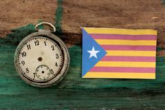 Old clock and flag of Catalonia on wood background. Image royalty free stock photography